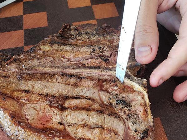 Retirando o osso do T-Bone com faca especial para carne e churrasco